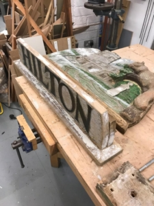 The village sign being reassembled